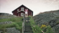 A woman walking down the stairs outdoors Huvudskr Stockholm archipelago Sweden.