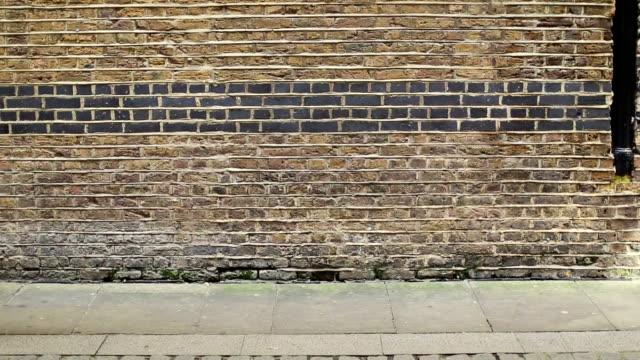 Donna cammina davanti a un muro di mattoni