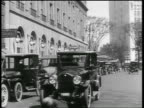 B/W 1919 woman walking in front of car on street + gets hit / driver picks her up / newsreel