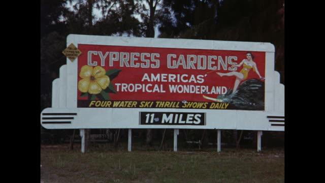 1954 HOME MOVIE Woman walking in grapefruit field / Grapefruit harvest / Tourist sign for Cypress Gardens / Winter Haven, Florida