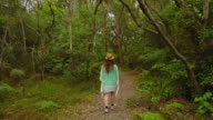 Woman walking in the forest, at Huskisson, Jervis Bay, Australia.