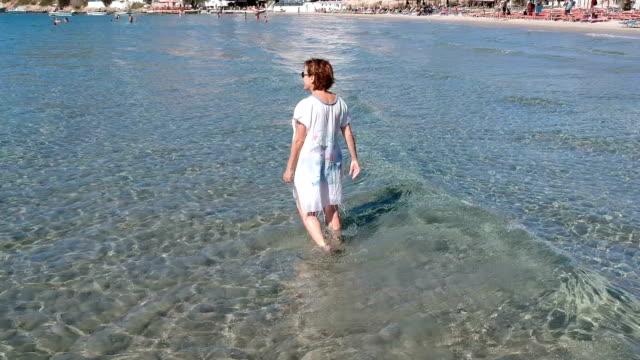 Wandelen in de ondiepe zee vrouw