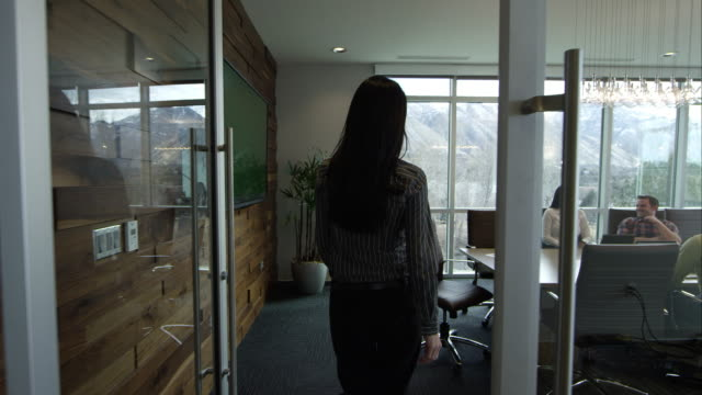 Woman walking into conference room.