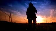 HD-Frau zu Fuß in den Sonnenuntergang mit Gewehr