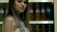 Woman walking near shelves with fizzy drinks in supermarket