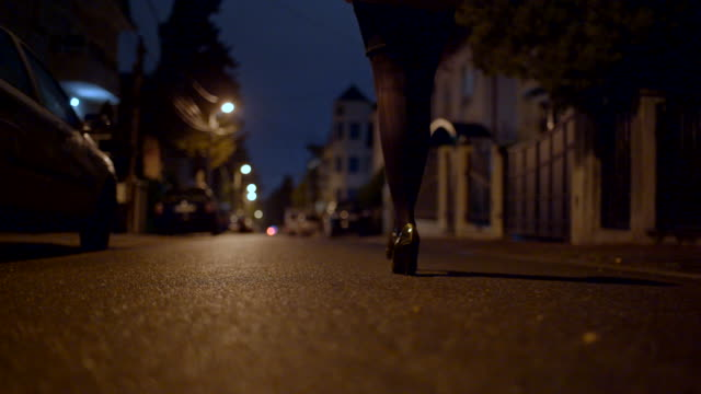 Woman walking on a street at night