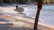 WS Woman walking on Caribbean beach / English Harbor, Antigua and Barbuda