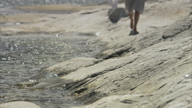 A woman walking on cliffs Huvudskar Stockholm archipelago Sweden.