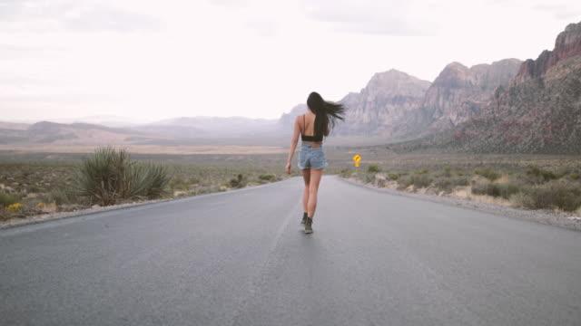 Woman walking on middle of street in desert