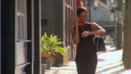 MS, TD, Woman walking on street and talking on mobile phone, Richmond, Virginia, USA