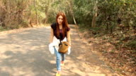 Woman walking on the road in forest