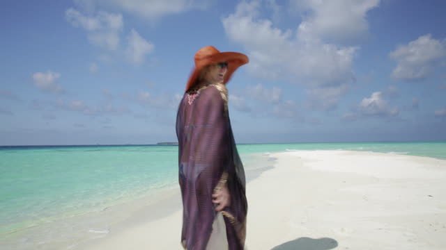 Woman walking on the sandbank with smile