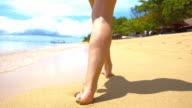 SLO MO Donna cammina sulla spiaggia tropicale