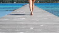 Frau zu Fuß auf hölzernen Dock auf der Insel