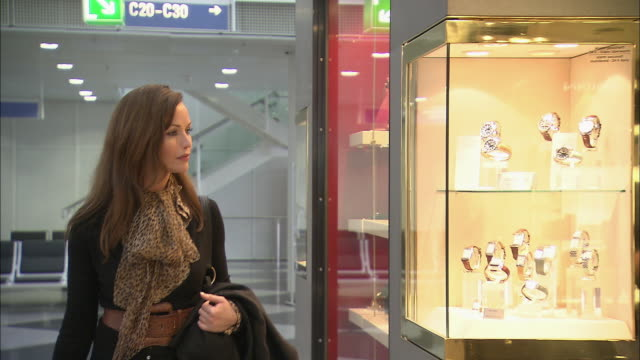 MS Woman walking past wristwatches and jewelry window displays in airport store / Munich, Germany