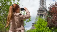 Woman walking the streets of Paris and taking pictures of Eiffel Tower