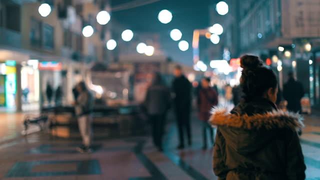 Woman walking through city crowd