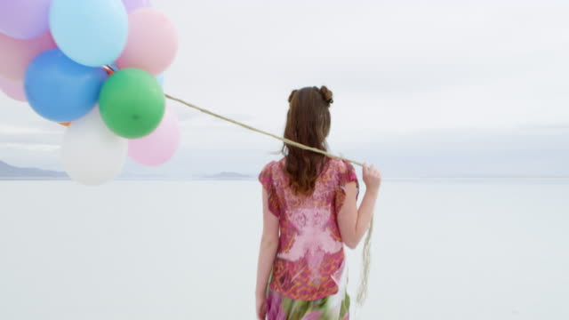 MS Woman walking through shallow water in desolate landscape holding colorful balloons