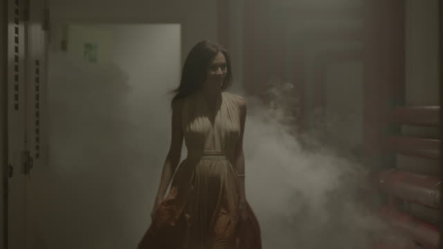 Woman walking through steam in basement corridor.