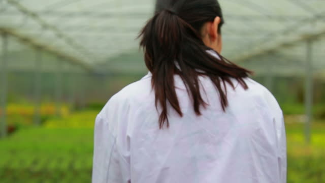 Woman walking through the greenhouse holding a clipboard