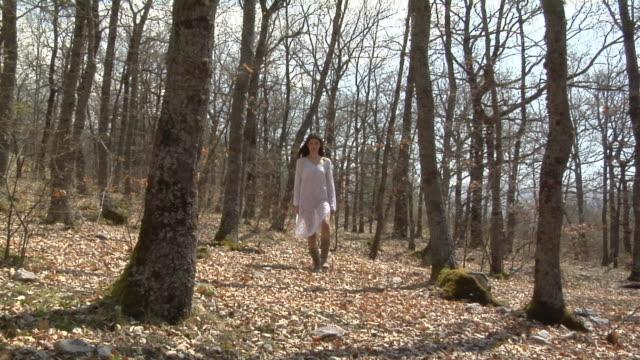 WS TU Woman walking through trees towards camera, Campo Imperatore, Abruzzo, Italy