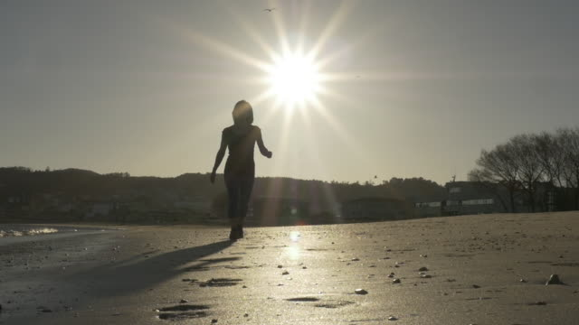 Woman walking to the camera with the sun in the back