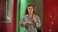 Woman walking toward camera unzipping mechanic's uniform to reveal red push-up bra