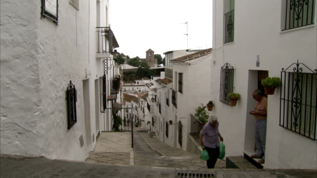 A woman walking up steep steps carrying shopping bags