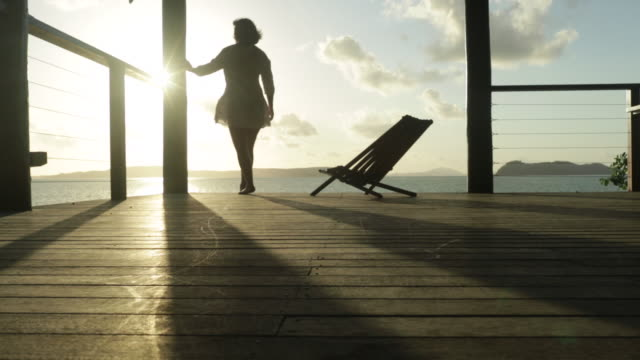 Woman walks across veranda and looks out to sea.