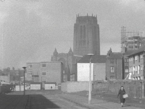 A woman walks along a quiet street with Liverpool Cathedral in the distance 1964