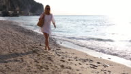 Woman walks along beach, carrying bag