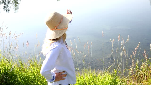 Woman walks along edge of mountain pond
