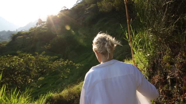 Woman walks along mountain trail, volcano behind