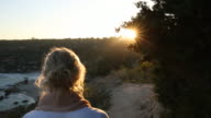 Woman walks along pathway towards beach, sunrise
