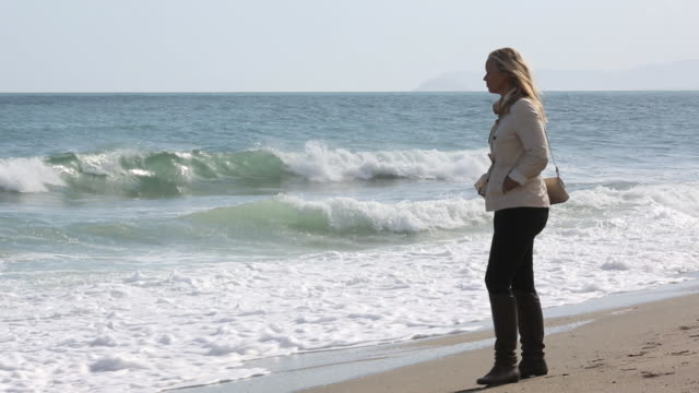 Woman walks along sandy beach, sends text on phone