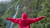 Woman walks below rainforest waterfall, in mist