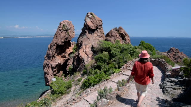 Woman walks down a stone staircase at Red Rocks of Cote d`Azur