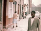 A woman walks from one shop to another in the Butetown area of Cardiff 1968