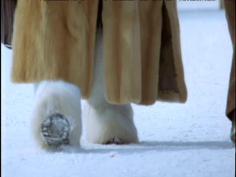 Woman walks in fur coat and boots Saint Moritz
