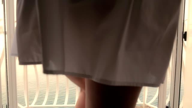 HD DOLLY: Woman Walks On A Balcony At Sunrise