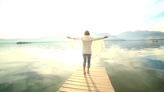 Woman walks on jetty, arms outstretched