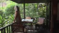 PAN / A woman walks out of a bungalow on a veranda in a tropical garden