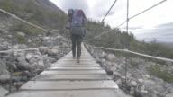 Woman walks over suspension bridge