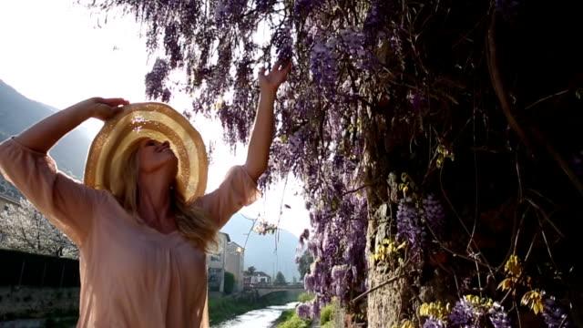 Woman walks past wisteria blossoms, pauses to enjoy perfume