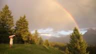 Woman walks through mountain meadow below rainbow, cat follows