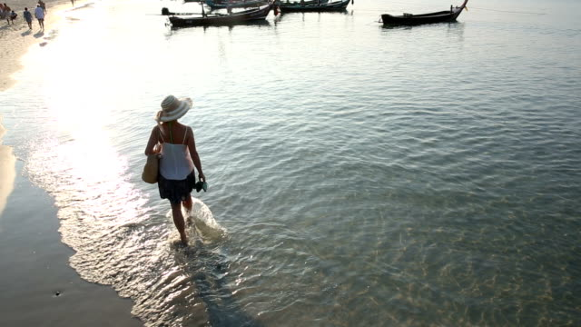Woman walks through shallows, towards distant boats