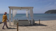 A woman walks to a beach cabana and looks out to the sea