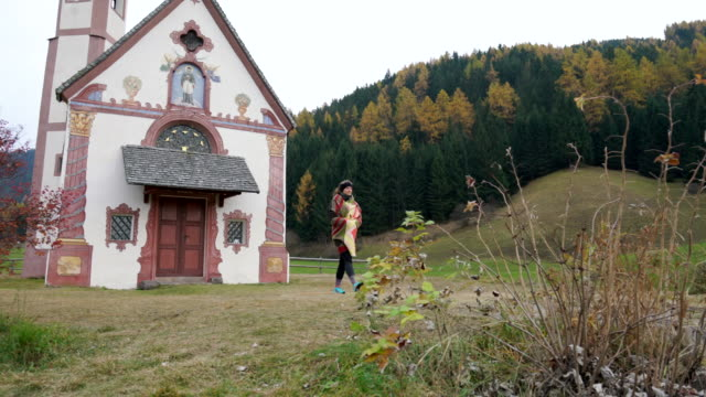 Woman walks towards small church at the end of valley