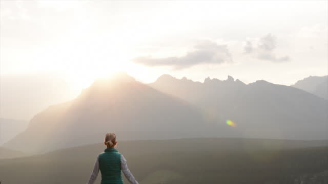 Woman walks up mountain slope above valley, extends arms