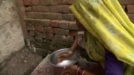Woman washes her face and feet with water from basin, Agra, Uttar Pradesh, India